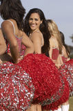 Cheerleaders In A Row. Cheerleaders in row with portrait of a smiling teammate looking over shoulder Royalty Free Stock Photos