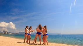 Cheerleaders run out perform Scale Basket Toss on beach stock video footage