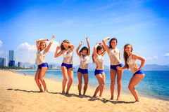 Cheerleaders stand on beach laugh wave hands against azure sea Royalty Free Stock Photo