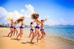 Cheerleaders stand in line hands over head in shallow water Royalty Free Stock Photos