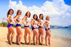 Cheerleaders stand in line hands on shoulders on beach. Cheerleaders in white blue uniform stand tip-toe in line with hands on shoulders hips on sand beach royalty free stock photography
