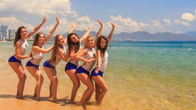 Cheerleaders stand in shallow water wave hands send kisses stock video footage