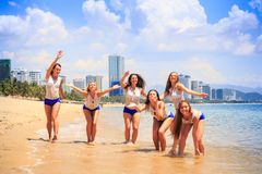 Cheerleaders stand in shallow water wave hands send kisses Royalty Free Stock Photos