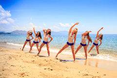 Cheerleaders stand in triangle hands over head on wet sand Stock Photo