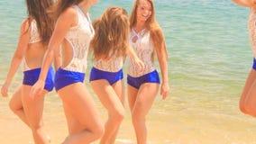Cheerleaders in uniform jump gambol in shallow water against sea stock video