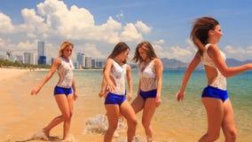 Cheerleaders in uniform jump gambol wave hands in shallow water. Cute cheerleaders in white blue uniform jump gambol wave hands in shallow water on beach against stock video