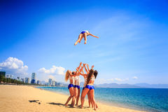 Cheerleaders in uniform perform Toe Touch Basket Toss on beach. Cheerleaders in white blue uniform perform Toe Touch Basket Toss on beach against azure sea wind Stock Photography