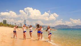 Cheerleaders in uniform run gambol about shallow water on beach. Cute cheerleaders in white blue uniform run and gambol about shallow water on beach against stock video footage