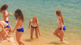 Cheerleaders in uniform run jump wave hands in shallow water. Cute cheerleaders in white blue uniform run jump wave hands in shallow water against azure sea wind stock video footage