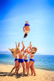 Cheerleaders in white blue perform Back Tuck Basket Toss on beach Royalty Free Stock Image