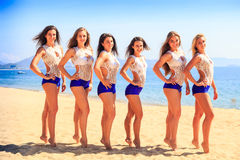 Cheerleaders in white blue stand in line on beach against sea Royalty Free Stock Photos