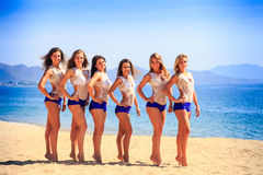 Cheerleaders in white blue stand in line on beach against sea Stock Images