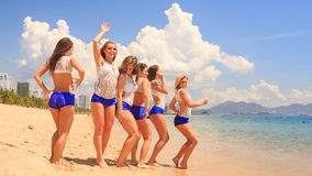 Cheerleaders in white blue stand in line run into water on beach stock video