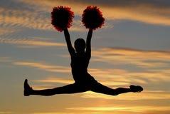 Cheerleaderschattenbild, das in einer Luft tut die Spalten mit einer SU springt Lizenzfreie Stockfotos