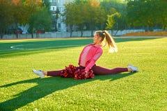 Cheerleading flicka i en tvinnagenomkörare, i morgonen på soluppgång på ett fält utomhus Sport hälsa, kondition royaltyfria foton