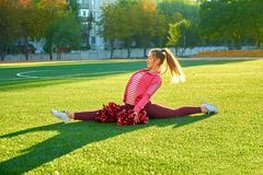 Cheerleading girl in a twine workout, in the morning at sunrise on a field outdoors. Sport, health, fitness royalty free stock photos