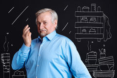 Cheerless aged man standing in the dirty kitchen. Absolute mess. Cheerless grey haired aged man standing in the dirty kitchen and waving his hand while disliking Royalty Free Stock Image