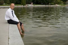 Cheerless businessman sitting by lake Royalty Free Stock Image