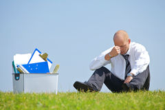 Cheerless businessman sitting next to basket full of files in park Stock Photography
