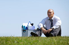 Cheerless businessman sitting next to basket full of files in park Stock Image