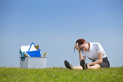 Cheerless businesswoman sitting next to basket full of files in park Stock Image