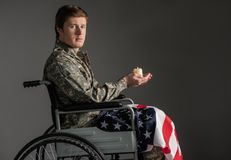 Unhappy paralyzed military man feeling helpless. Cheerless disabled soldier looking at camera with sad look and sitting in wheelchair. He is having candle in Royalty Free Stock Photos