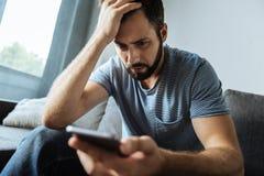Cheerless gloomy man holding his smartphone Stock Images