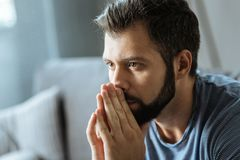 Cheerless handsome man feeling depressed. Difficult times. Cheerless nice handsome man holding his hands together and thinking about his problem while feeling Royalty Free Stock Image