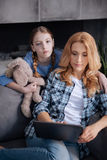 Cheerless little girl waiting for mother attention at home. Bored from waiting for you. Sad unhappy lonely girl waiting for mother attention at home and hugging Royalty Free Stock Photo