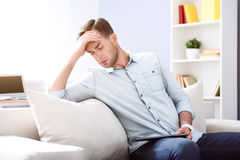 Cheerless man sitting on the couch Stock Image