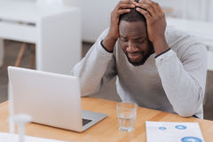 Cheerless moody man suffering from headache. Awful pain. Cheerless moody adult man holding his head and suffering from the headache while being tired Royalty Free Stock Images