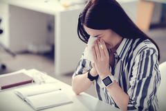 Cheerless nice woman having flu. Unpleasant disease. Cheerless nice business woman holding a paper tissue and sneezing while having a flu Royalty Free Stock Photos