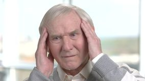 Cheerless old man having strong headache. Sad aged man massaging his temples as suffering from headache stock footage