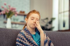 Cheerless pale young girl rubbing her face. Ill child. Cheerless pale girl rubbing her face while feeling ill stock photos