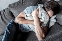 Cheerless sad man crying in the cushion. Too emotional. Cheerless depressed sad man feeing unhappy and crying in the cushion while lying on the sofa stock photos