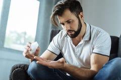 Cheerless sad man taking medicine Stock Images