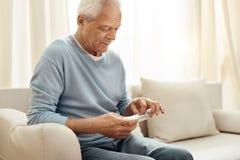 Cheerless senior man holding a pill organizer Royalty Free Stock Photos