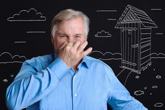 Cheerless senior man putting his hand to the nose. Unpleasant smell. Cheerless unhappy man putting his hand to the nose and trying not to breathe while being Royalty Free Stock Image
