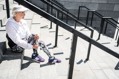 Cheerless senior woman resting after climbing up stadium ladder outdoor. Sad old lady is sitting on stone stairs with metal guard rails and looking far to stock photo