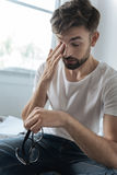 Cheerless tired man rubbing his eye Stock Images