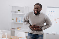 Cheerless unhappy man suffering from pain. Strong stomachache. Cheerless unhappy nice man holding his stomach and suffering from pain while having food poisoning Royalty Free Stock Photos
