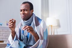 Cheerless unhappy man taking medicine. My treatment. Cheerless unhappy moody man holding a glass of water and taking a pill while sitting at home Stock Image