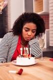 Cheerless unhappy woman having a sad birthday celebration stock image