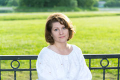 Cheerless woman in park on a bench Royalty Free Stock Photography