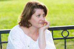 Cheerless woman in park on a bench Royalty Free Stock Photo