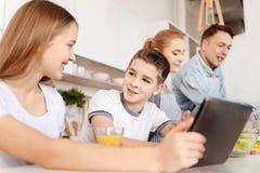 Cheerrful syskon som sitter i köket genom att använda minnestavlan arkivbild