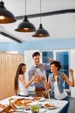 cheers Счастливые друзья веселя пивные бутылки внутри помещения партия cele Стоковая Фотография RF