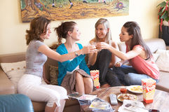 Cheers. Four girls having a party in a livingroom Stock Images