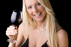 Cheers. A young woman with a glass of red wine gives you a toast Stock Photo