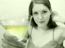 Cheers 2. Woman holding martini glass in camera, smiling. Focus on glass stock images